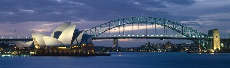 australia, new south wales, sydney, the opera house and harbour bridge lit up at dusk.
