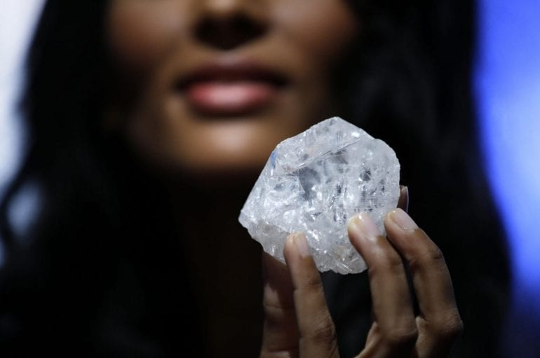 A model displays a large diamond at Sotheby's in New York, Wednesday, May 4, 2016. The diamond the size of a tennis ball — the largest discovered in over a century — could sell for more than $70 million, auctioneer Sotheby's said. (AP Photo/Seth Wenig) ORG XMIT: NYSW105