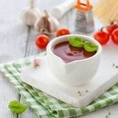 Fresh homemade tomato sauce in a white bowl on a white board, closeup, selective focus